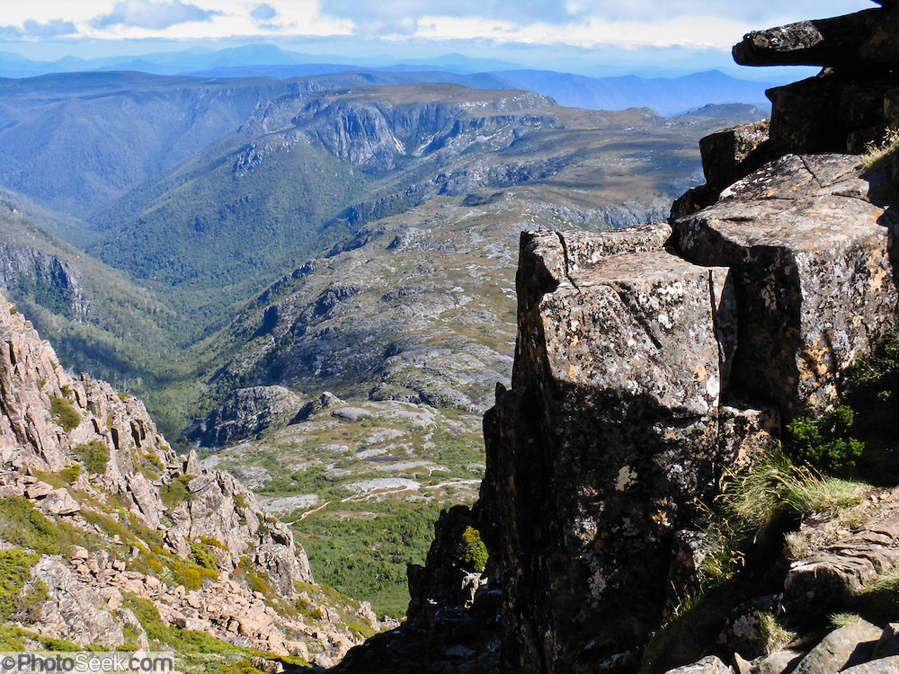 A track leads to the top of Cradle Mountain (1545 m or 5069 ft) in Cradle Mountain - Lake Saint Clair National Park, Tasmania, Australia. The Tasmanian Wilderness was honored as a UNESCO World Heritage Site in 1982, expanded in 1989. The most extensive dolerite formations in the world dominate the landscape of Tasmania, where magma intruded into a thin veneer of Permian and Triassic rocks over perhaps a million years during the Jurassic breakup of supercontinent Gondwana in the Southern Hemisphere, forming vast dolerite/diabase sills and dike swarms. (North American geologists use the term diabase instead of dolerite to refer to the fresh, unaltered rock.)