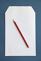 Pencil and blank paper over dark blue surface