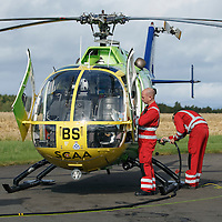National Air Ambulance Week.. Britain's last Bolkow helicopter air ambulance operated by SCAA prepares to fly into history when it is replaced by EC-135 in November 2015. To mark this Scotland's original Bolkow paramedics gathered at Perth Airport to meet the current crew.<br /> Pictured Captain Russell Myles Senior Pilot (left) prepares Helimed 76 for flight with paramedics John Salmond and Mark Tynon<br /> Picture by Graeme Hart.<br /> Copyright Perthshire Picture Agency<br /> Tel: 01738 623350  Mobile: 07990 594431