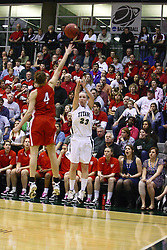 18 March 2011: Olivia Lett puts up a long duece as Kathryn Berger attempts a block during an NCAA Womens basketball game between the Washington University Bears and the Illinois Wesleyan Titans at Shirk Center in Bloomington Illinois.