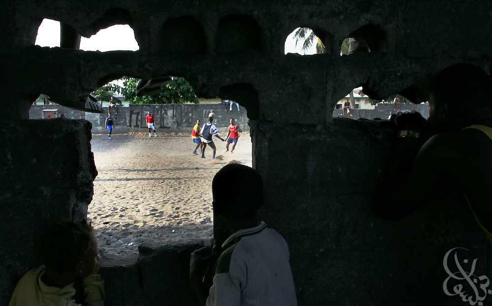 """Supporters watch through a hole in a wall as the """"Almighties of Koomassi"""" academy football club practices in the Koomassi neighborhood of Abidjan, Côte d'Ivoire February 17, 2006.  Trying to mimic the successes of ASEC academy, more than 300 rival football academies have been started in Abidjan. Parents hoping of their children will become national team members or pro european league players often become indebted in order to put their children into the copycat academies, which focus on football skills, but do little to educate the young Ivorians who attend them."""