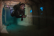Roatan, Honduras - A diver models for me inside the Prince Albert shipwreck. I attached a strobe to the back of her tank and had her hold a Triggerfish sensor to make the strobe fire behind her, lighting up the background. Diver: Holly Johnston.