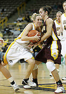 25 JANUARY 2007:  Iowa guard Kristi Smith (11) tries to drive past Minnesota guard Brittany McCoy (12) in Iowa's 80-78 overtime loss to Minnesota at Carver-Hawkeye Arena in Iowa City, Iowa on January 25, 2007.
