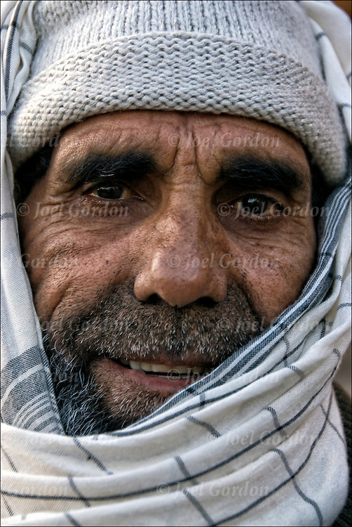 Head and shoulder portrait of Pakistani male wearing hat and headscarf making eye contact with camera.