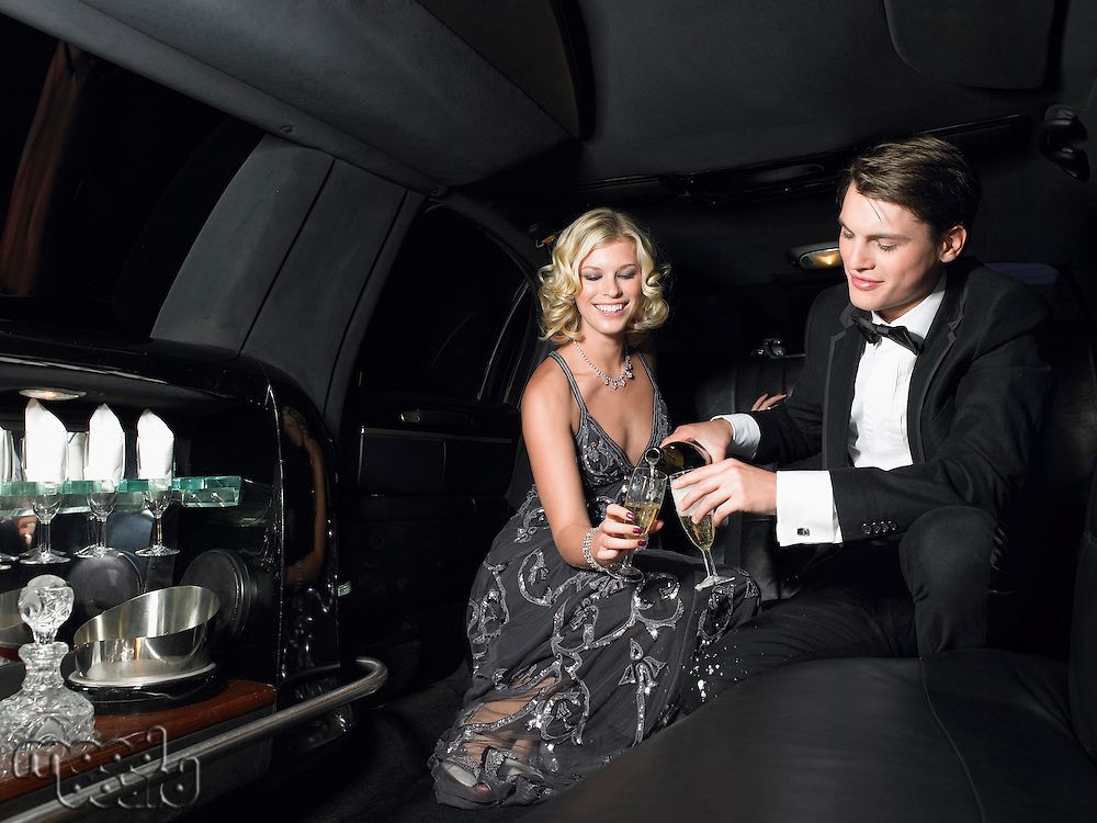 Couple in back of limousine drinking champagne