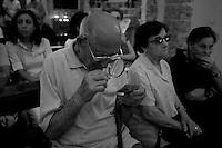 Un anziano fedele all'interno della chiesa dell'Arcangelo Michele, situata nel paesino di Mesagne (Br), con l'aiuto di una lente d'ingrandimento, legge una preghiera sul retro di un santino raffigurante la Madonna del Carmine.
