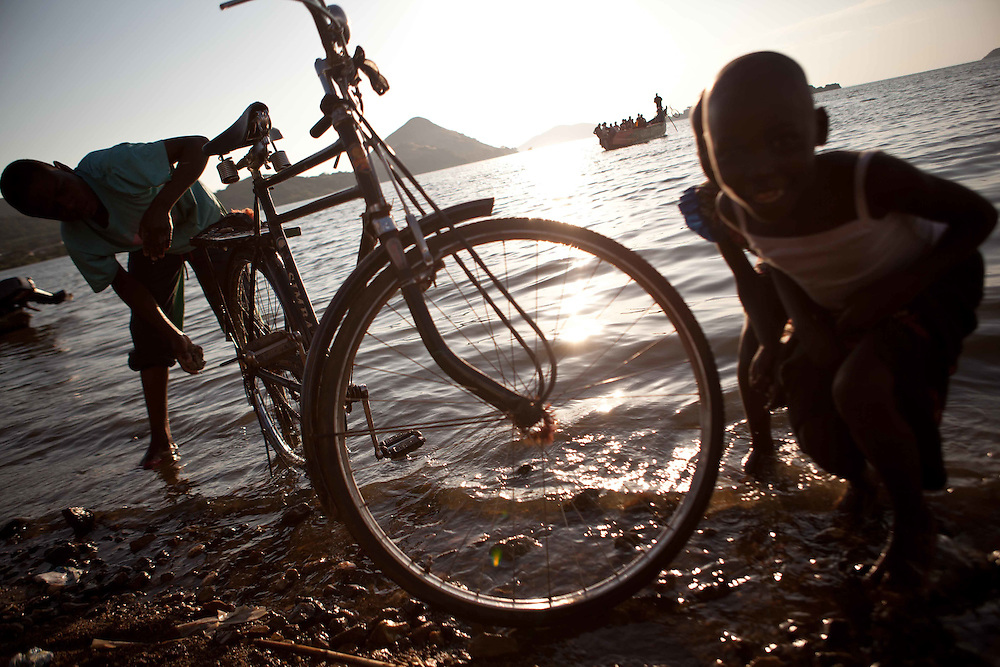 Children crouch along the shores of Lake Victoria, as boats sail away towards adjacent islands and a local man washes his bike.