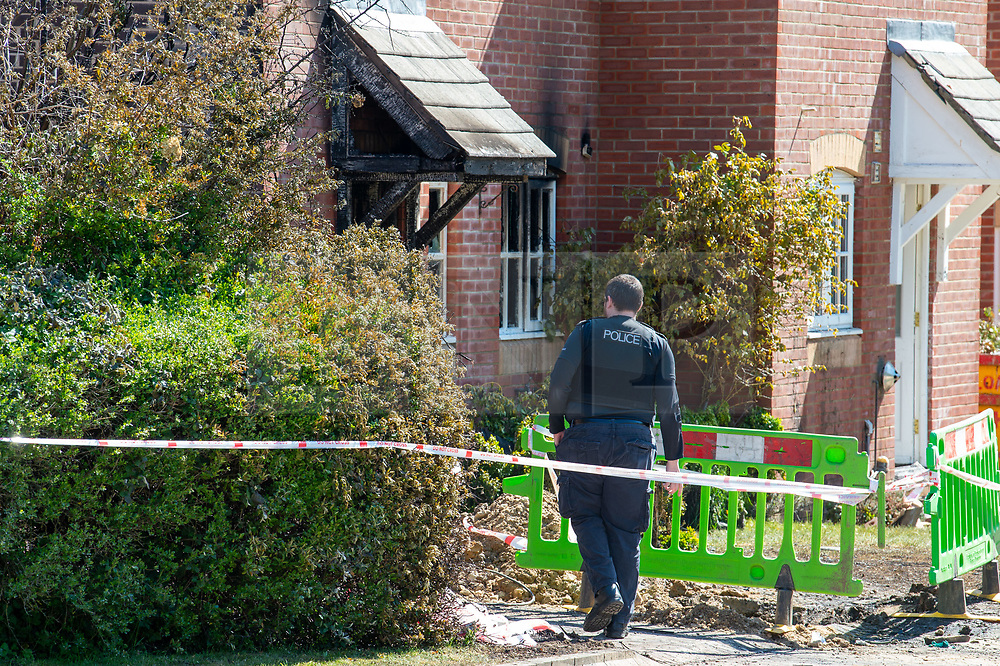 © Licensed to London News Pictures. 06/05/2020. Woolton Hill, UK. A police officer from the Hampshire Constabulary looks toward the front door of a house gutted by fire. A fire has destroyed two houses on Woolton Lodge Gardens, Woolton Hill in Hampshire. The fire started approximately 20:10 BST on Tuesday 05/05/2020. Photo credit: Peter Manning/LNP