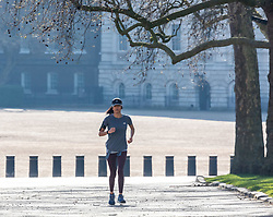 © Licensed to London News Pictures. 25/03/2020. London, UK. A women exercises in St James's Park during lockdown as Prime Minister Boris Johnson orders police to enforced the new rules. Prince Charles is confirmed to have contracted Covid19 as the crisis continues. Photo credit: Alex Lentati/LNP