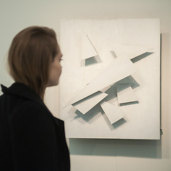 London, UK - 15 October 2014: a woman looks at 'Blanc sur Blanc' by Jean Tinguely  during the first day of Frieze Art Fair and Frieze Masters in Regent's Park.