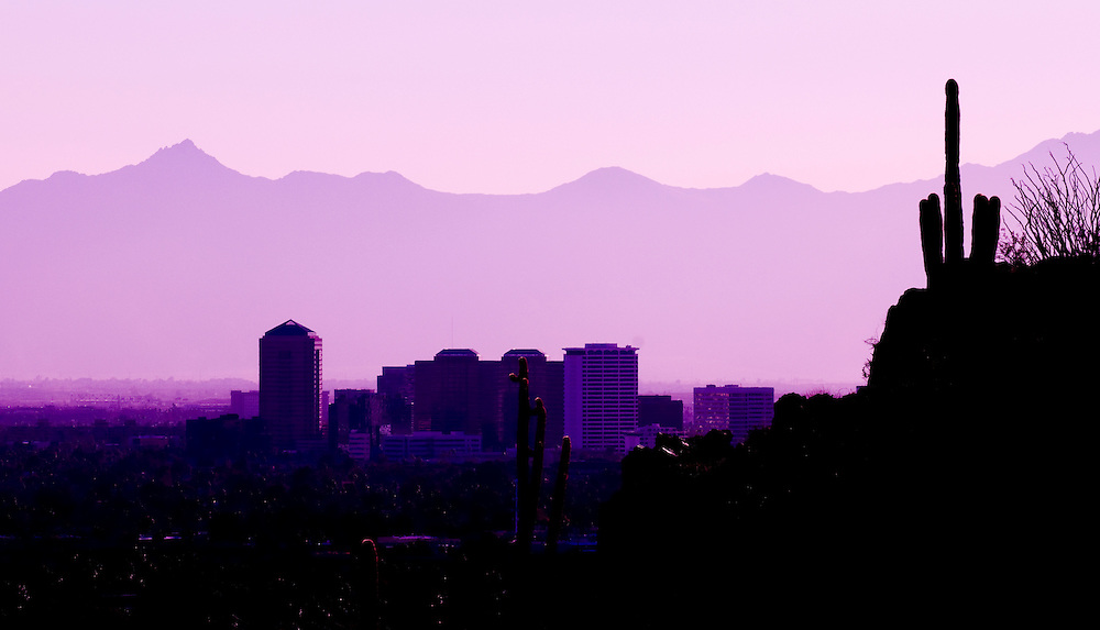 The Phoenix skyline at dusk as seen from a hiking trail leading to Piestewa Peak in Phoenix, Arizona.