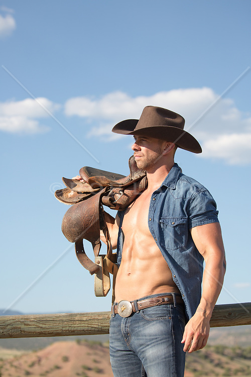cowboy with open shirt carrying a saddle over his shoulder