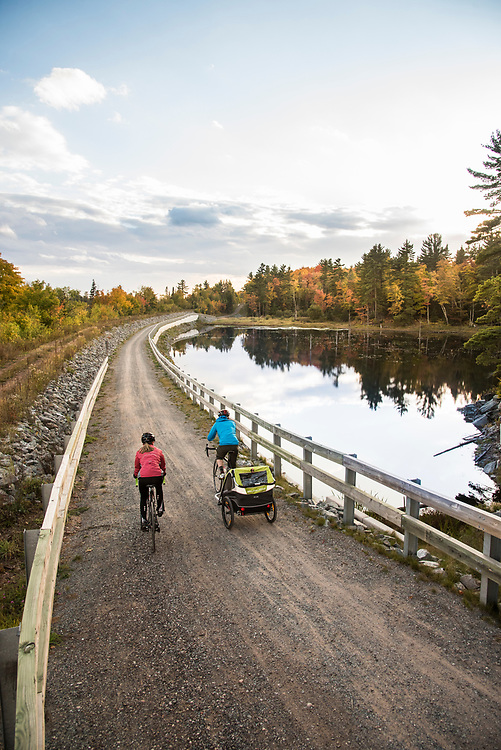 Family biking near a pond along the Iron Ore Heritage Trail, a multiuse recreation trail connecting communities in Marquette County on Michigan's Upper Peninsula.