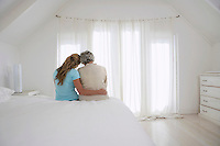 Rear view of adult daughter with her arm around mother in white bedroom