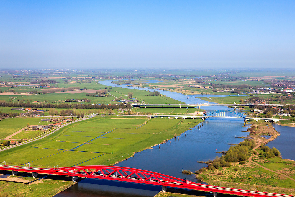 Nederland, Gelderland - Overijssel, Hattem, 01-05-2013; IJsselbrug, spoorbrug bij Hattem voor de Hanzelijn. In de achtergrond de brug voor regionaalautoverkeer en de brug in rijksweg A28 naar Zwolle.<br /> De 'Hanzeboog' is ontworpen door  Quist Wintermans Architecten.<br /> Bridges over the river IJssel near Zwolle. The red railway bridge Hanzeboog (Hanseatic arch) over the IJssel near Zwolle, has been designed by Quist Wintermans Architects.  <br /> luchtfoto (toeslag op standard tarieven);<br /> aerial photo (additional fee required);<br /> copyright foto/photo Siebe Swart