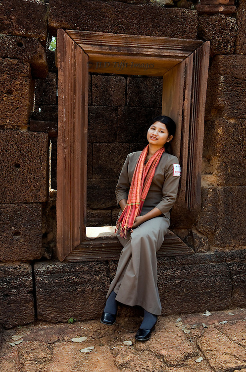 Yound woman wearing the official guard uniform of a long grey dress with shoulder insignia, over which she has draped a dark pink scarf.  She is seated in a window embrasure at one of the Angkor temples (Banteay Srei).  She wears a faint but serene smile.