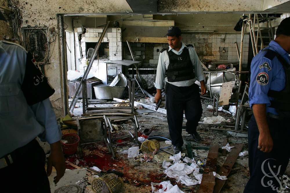 Iraqi policemen investigate the bombed out and blood soaked interior of a restaurant where 13 people were killed and 17 wounded in an attack in the Karrada district of Baghdad, Iraq, on Sunday, May 17, 2006. The restaurant was a popular lunch spot for policemen from a station just 50 yards away, and three policemen were among those killed in the attack by a suspected suicide vest bomber.