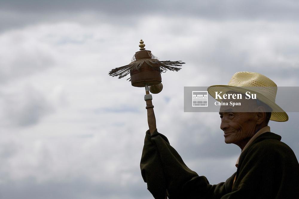 Tibetan pilgrim pray with praying wheel, Litang, Sichuan-Tibet, China