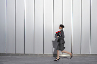 hurrying Businesswoman running past building side view