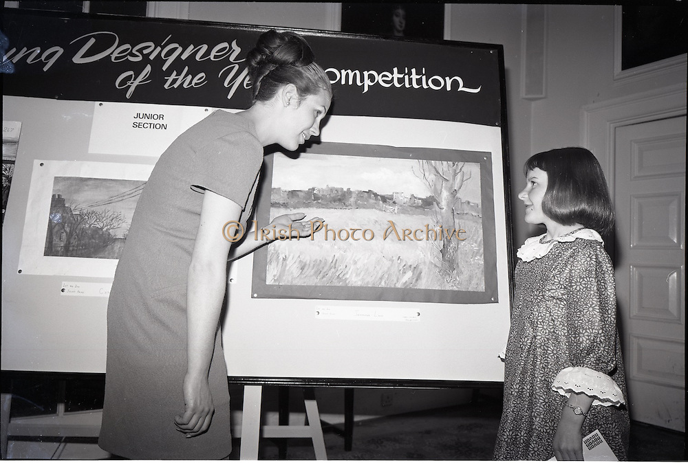"""28/06/1967<br /> 06/28/1967<br /> 28 June 1967<br /> Presentation of prizes at Navan Carpets """"Young Designer of the Year"""" reception in the Royal Hibernian Hotel, Dublin. Image shows Miss Elizabeth Fogarty, Navan Carpets Ltd. with Miss Jennifer Lane, Balbriggan who won joint 1st and 2nd prize in the Junior Section, in front of her design."""