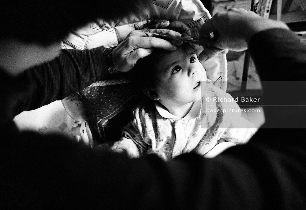 """Losing the hair I was born with."" We look over the darkened shoulder of a mother as she cuts her baby daughter's hair, at home, for the first time. Sitting in her high-chair, the child watches with fascination as the scissors snip away at the tufts of thick, dark hair the girl has had from birth. The experience is clearly enchanting her and she looks with her mouth open, captivated by this strange instrument that she feels trimming her head. This is from a documentary series of pictures about the first year of the photographer's first child Ella. Accompanied by personal reflections and references from various nursery rhymes, this work describes his wife Lynda's journey from expectant to actual motherhood and for Ella - from new-born to one year-old."