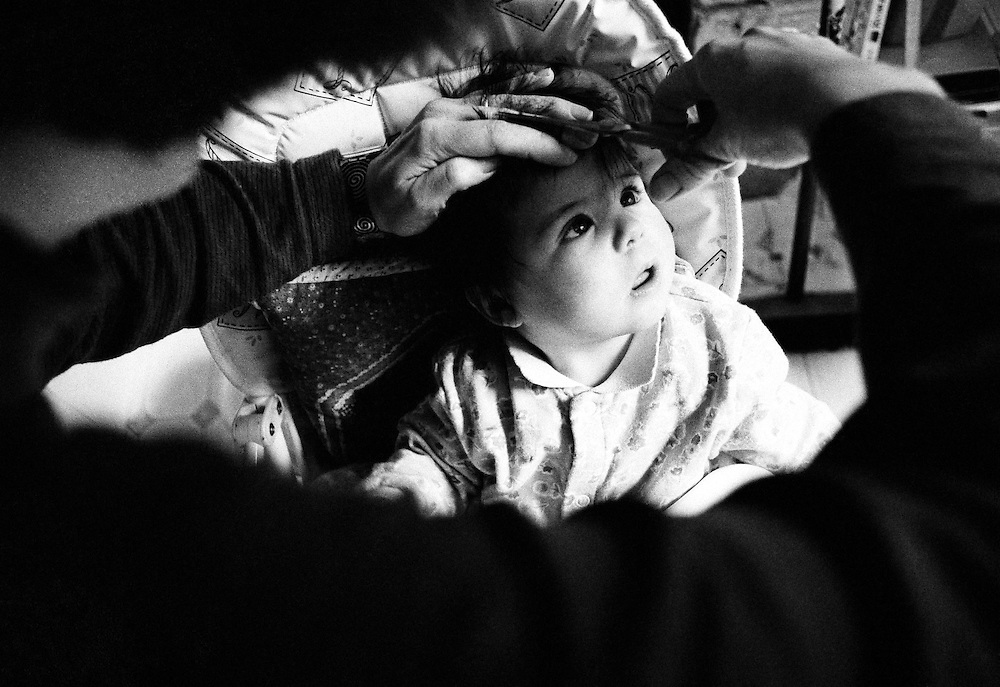 """""""Losing the hair I was born with."""" We look over the darkened shoulder of a mother as she cuts her baby daughter's hair, at home, for the first time. Sitting in her high-chair, the child watches with fascination as the scissors snip away at the tufts of thick, dark hair the girl has had from birth. The experience is clearly enchanting her and she looks with her mouth open, captivated by this strange instrument that she feels trimming her head. This is from a documentary series of pictures about the first year of the photographer's first child Ella. Accompanied by personal reflections and references from various nursery rhymes, this work describes his wife Lynda's journey from expectant to actual motherhood and for Ella - from new-born to one year-old."""