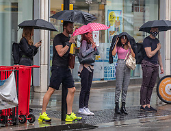 © Licensed to London News Pictures. 25/08/2020. London, UK. Commuters on their way in to work get caught in heavy rain in Fulham Broadway in South West London this morning. The Met Office has issued a yellow weather warning for Storm Francis with winds in excess of 50mph and heavy rain for most of the country which could lead to potential travel disruption and damage to trees. Photo credit: Alex Lentati/LNP