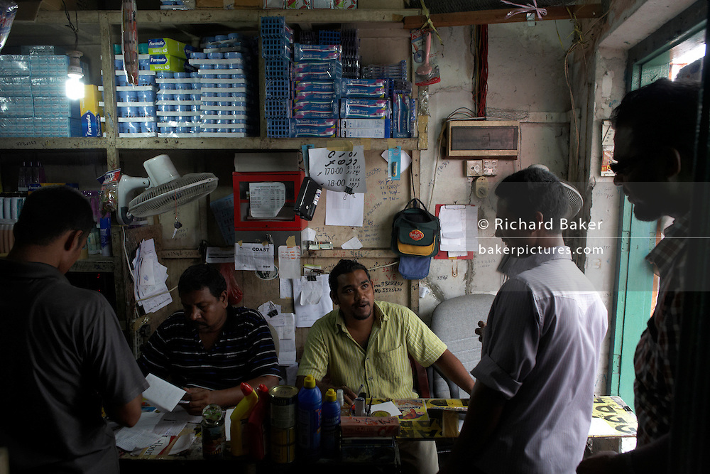 A crowded business dealing in cash from street customers buying sundries in a side street in Male, Maldives.