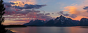 At Jackson Lake, sunrise illuminates clouds with orange, pink, and magenta light. Grand Teton National Park contains the major peaks of the 40-mile (64 km) Teton Range and part of the valley known as Jackson Hole, in Wyoming, USA. A parkway connects 10 miles north to Yellowstone National Park. Surrounding parkland and National Forest constitute the Greater Yellowstone Ecosystem, one of the largest intact mid-latitude temperate ecosystems in the world.  Three overlapping images were stitched to make this panorama.