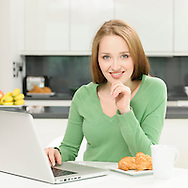 Attractive young woman working from home using her laptop computer at kitchen table