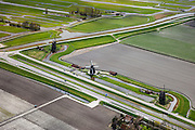 Nederland, Noord-Holland, Gemeente Schermer, 16-04-2012; Schermerhorn, molengang aan de Noordervaart. In verband met het niveauverschil tussen de polder Schermer (rechts van de molens) en de boezem (de ringvaart, loodrecht op de vaart) zijn opeenvolgende molens nodig om het water vanuit de polder uit te slaan. De Eilandspolder, met onregelmatige verkaveling, op het tweede plan. Ten tijde van de drooglegging van de polder stonden hier zes molens, de oorspronkelijk molengang is later gewijzigd (feitelijk is er geen sprake van een molendriegang maar een onvolledige dubbele tweegang)..Schermerhorn, mill network next at the Noordervaart (North Canal). Due to the difference in level between the polder Schermer (right of the mills) and the 'bosom' (the ring canal, perpendicular to the North Canal) successive mills are necessary to pump away the water..luchtfoto (toeslag), aerial photo (additional fee required);.copyright foto/photo Siebe Swart