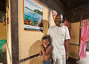 "Lobo Village community member Bram Wariensi and his son show off a conservation poster distributed by RARE Conservation and Conservation International, which they proudly displays in their home. The poster celebrates a locally designated ""Fish Savings Area"" as the first no take zone in the Kaimana Marine Consersation Area."