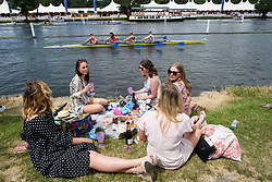 © Licensed to London News Pictures. 04/07/2018. Henley-on-Thames, UK. A group of women enjoy lunch on the bank of the river on day one of the Henley Royal Regatta, set on the River Thames by the town of Henley-on-Thames in England. Established in 1839, the five day international rowing event, raced over a course of 2,112 meters (1 mile 550 yards), is considered an important part of the English social season. Photo credit: Ben Cawthra/LNP