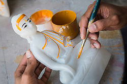 Asia, Myanmar, Mandalay. Hand painting marble Buddha in workshop.