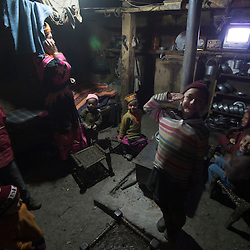 Bumburet, Chitral District,Pakistan.Pic Shows A Kalash family in their home in the valley of Bumburet making some traditional clothing