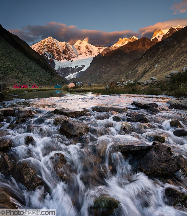 At Incahuain campground, Rio Jahuacocha flows from the melting glaciers of Mount Jirishanca (Icy Beak of the Hummingbird, 6126 m or 20,098 feet) at sunset. Day 8 of 9 days trekking around the Cordillera Huayhuash in the Andes Mountains, one day's walk from LLamac, Peru, South America. This panorama was stitched from 4 overlapping photos.