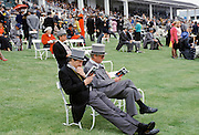 Racegoers studying form in front of the Grandstand at Epsom Racecourse for Derby Day, UK
