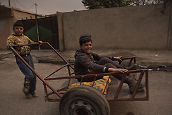 Licensed to London News Pictures. 08/11/2016. Qayyarah, Iraq. Two boys smile as they play with a handcart in the smoke filled city of Qayyarah, Iraq. Oil wells in and around the town of Qayyarah, Iraq, we set alight in July 2016 by Islamic State extremists as the Iraqi military began an offensive to liberated the town.<br /> <br /> For two months the residents of the town have lived under an almost constant smoke cloud, the only respite coming when the wind changes. Those in the town, despite having been freed from ISIS occupation, now live with little power, a water supply tainted with oil that only comes on periodically and an oppressive cloud of smoke that coats everything with thick soot. Many complain of respiratory problems, but the long term health implications for the men, women and children living in the town have yet to be seen. Photo credit: Matt Cetti-Roberts/LNP