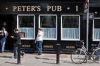 Man smoking and talking on mobile phone outside pub in Dublin Ireland