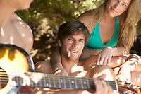 Young people in swimwear one playing guitar close up