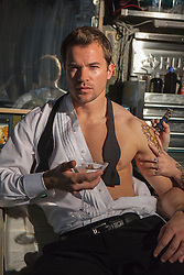 AlSexy man in an open tuxedo shirt holding a martini while getting a tattoo