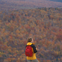 A hiker looks over late fall colors to the western horizon on Middle Sugarloaf Mountain.  White Mountain National Forest.  Fall. Twin Mountain, NH