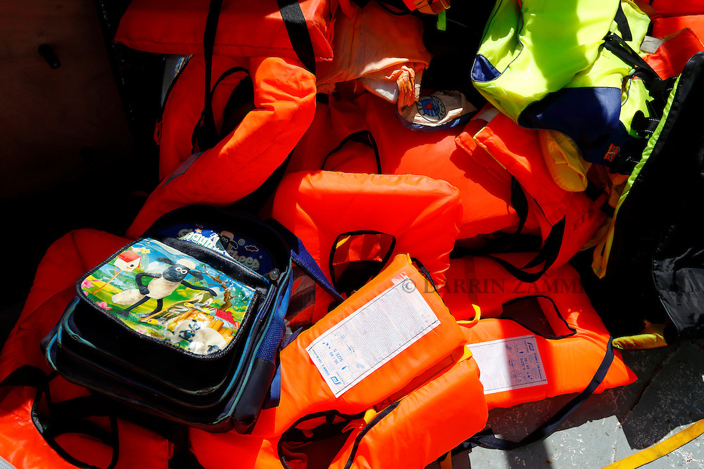 A child's bag lies on a pile of life jackets on the Migrant Offshore Aid Station (MOAS) ship MV Phoenix during a migrant rescue operation from an overloaded wooden boat 10.5 miles off the coast of Libya August 6, 2015.  An estimated 600 migrants on the boat were rescued by the international non-governmental organisations Medecins san Frontiere (MSF) and MOAS without loss of life on Thursday afternoon, a day after more than 200 migrants are feared to have drowned in the latest Mediterranean boat tragedy after rescuers saved over 370 people from a capsized boat thought to be carrying 600.<br /> REUTERS/Darrin Zammit Lupi <br /> MALTA OUT. NO COMMERCIAL OR EDITORIAL SALES IN MALTA