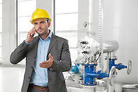 Young male engineer using cell phone in industry