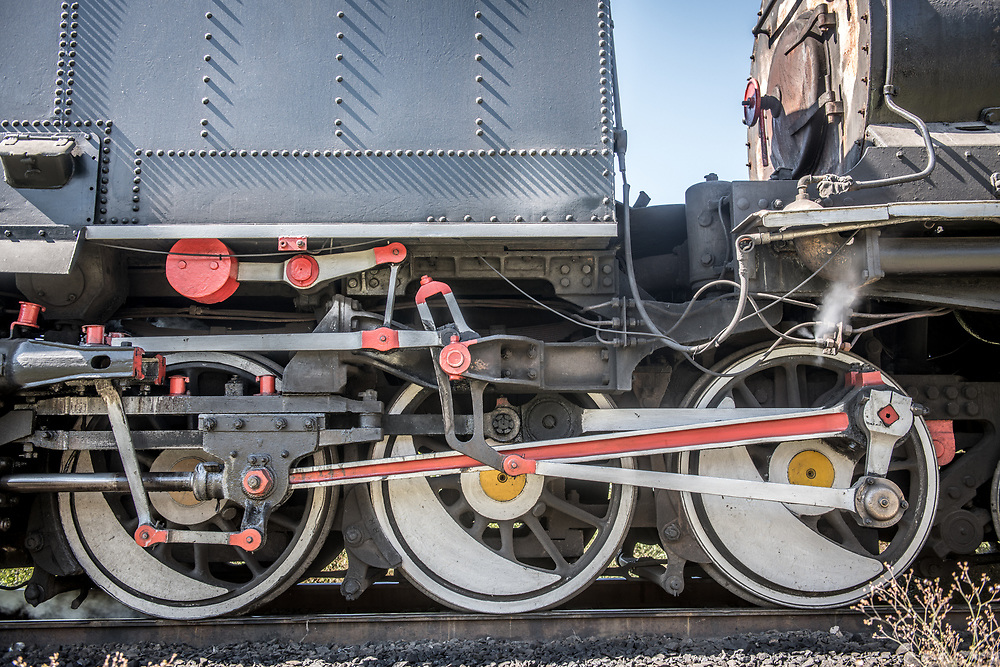 A close up of the wheels on a Garratt steam locomotive as it crosses the Victoria Falls Bridge. Zimbabwe