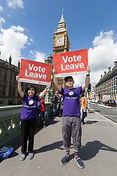 © Licensed to London News Pictures. 15/06/2016. LONDON, UK.  Two Vote Leave supporters with placards on Westminster Bridge. Nigel Farage led a pro-Brexit flotilla of fishing vessels along the River Thames to Westminster today, urging people to vote leave in the European Referendum.  Photo credit: Vickie Flores/LNP