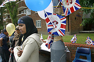 A young Muslim woman wearing a head scarf standing next to a Union Jack flag at a Golden Jubilee street party in Jubilee Street in the Stepney Green area of east London, where hundreds turned out to celebrate the 50 year reign of Queen Elizabeth II. Celebrations took place across the United Kingdom with the centrepiece a parade and fireworks at Buckingham Palace, the Queen's London residency. Queen Elizabeth ascended to the British throne in 1952 upon the death of her father, King George VI.