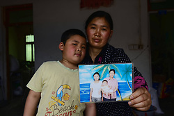 59601370  .The 41-year-old Lu Shaorong and her 7-year-old son Huang Haixu pose for photo with an old picture in the quake-hit Longmen Village, southwest China s Sichuan Province, May 4, 2013. The old picture of Lv with her daughter and son was taken at a photo studio in 2006. Old photos are not daily necessities for who just suffered a 7-magnitude earthquake, but they are still cherished as they recorded peoples past life and recalled memories, May 4, 2013.  Photo by: i-Images.UK ONLY
