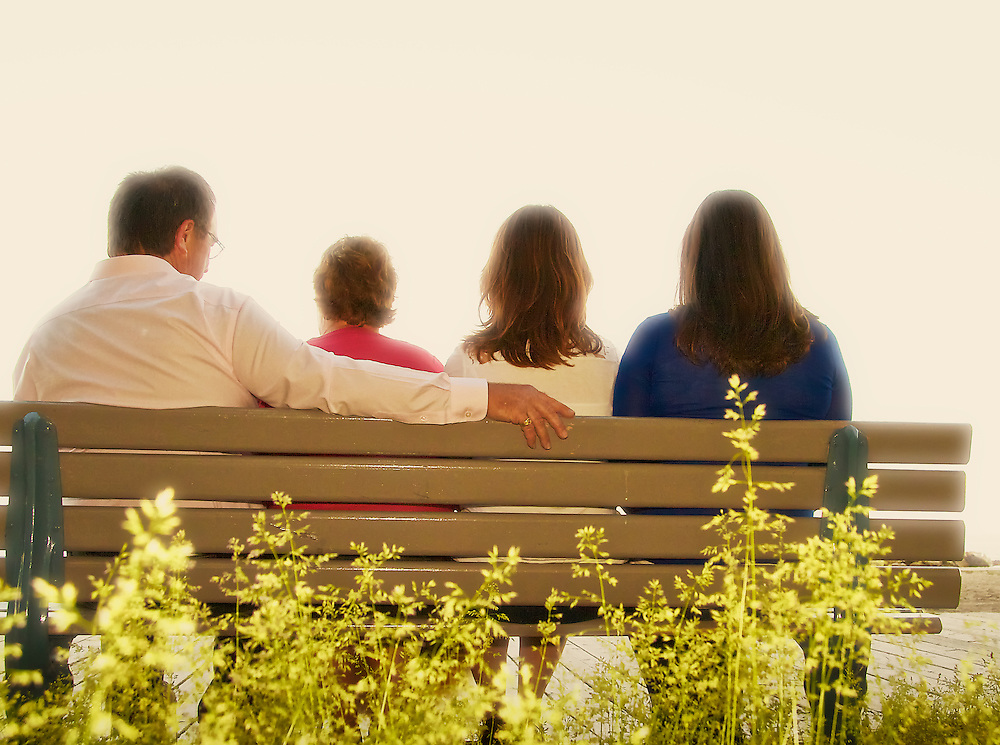 Family sitting on a boardwalk park bench during sunset, The Beach, Toronto (Canada)