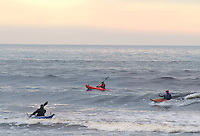 Surfers ride the waves in kayaks, on the West Coast of Vancouver Island at Jordan River.